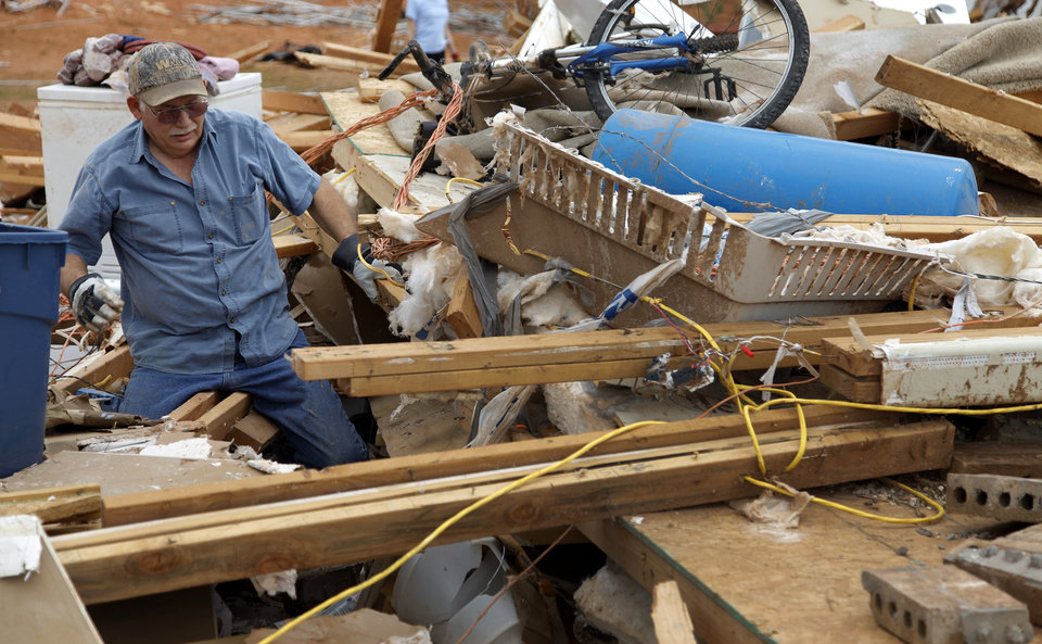 Photo - Tom Green tries to recover items from his daughter's house that was destroyed by Tuesday's tornado west of El Reno, Wednesday, May 25, 2011. Photo by Chris Landsberger, The Oklahoman