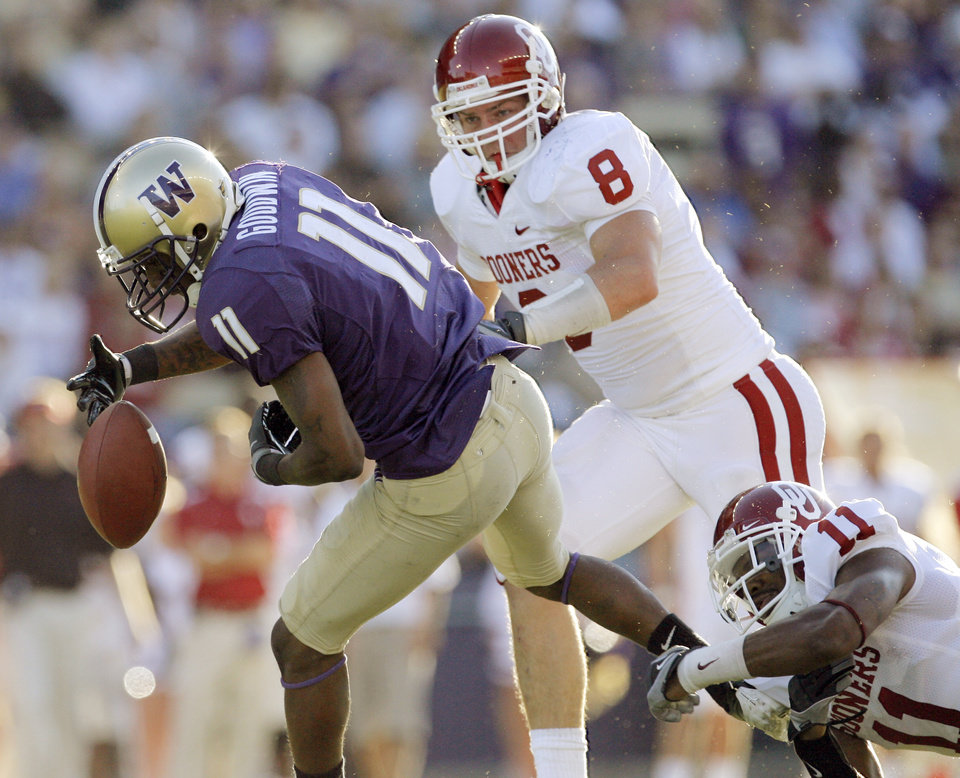 Photo - UW's D'Andre Goodwin (11) fumbles the ball after a catch as he is pursued by OU's Ryan Reynolds (8) and Lendy Holmes in the second quarter during the college football game between the University of Oklahoma (OU) and University of Washington at Husky Stadium in Seattle, Wash., Saturday, September 13, 2008. OU recovered the fumble. BY NATE BILLINGS, THE OKLAHOMAN ORG XMIT: KOD