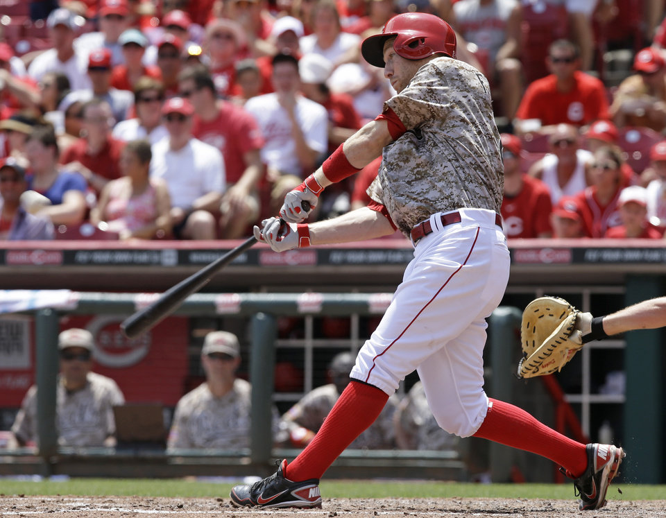 Photo - Cincinnati Reds' Todd Frazier hits a two-run home run off Toronto Blue Jays starting pitcher R.A. Dickey in the fifth inning of a baseball game on Sunday, June 22, 2014, in Cincinnati. (AP Photo/Al Behrman)