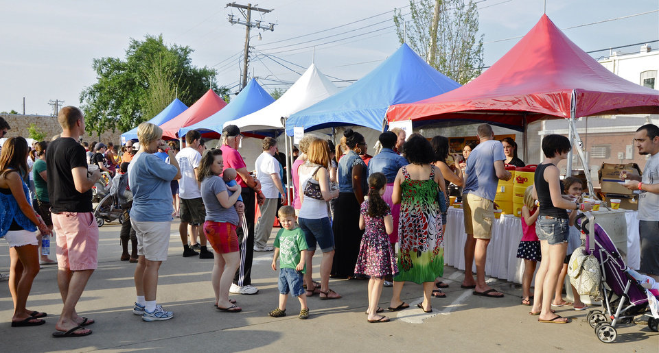 Photo - People wait in line to get a variety of goodies offered at this year's Taste of Edmond, part of LibertyFest celebrations. PHOTO BY M. TIM BLAKE, FOR THE OKLAHOMAN.  M. Tim Blake - FOR THE OKLAHOMAN