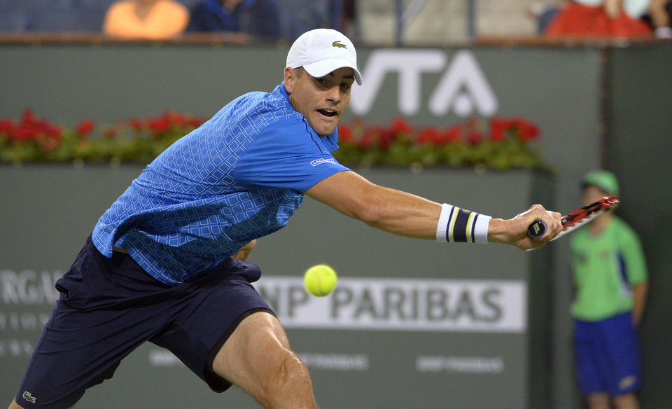 Photo - John Isner, of the United States, returns a shot to Lu Yen-Hsun, of Taiwan, at the BNP Paribas Open tennis tournament, Tuesday, March 11, 2014, in Indian Wells, Calif. (AP Photo/Mark J. Terrill)