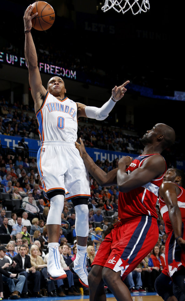 Oklahoma City's Russell Westbrook (0) goes to the basket past Washington's Emeka Okafor (50) during an NBA basketball game between the Oklahoma City Thunder and the Washington Wizards at Chesapeake Energy Arena in Oklahoma City, Wednesday, March 19, 2013. Oklahoma City won 103-80. Photo by Bryan Terry, The Oklahoman