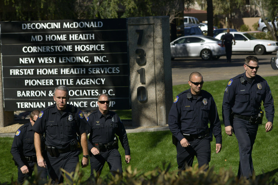 Photo - Police officers leave an office building after a shooting at the building in Phoenix on Wednesday, Jan. 30, 2013. A gunman opened fire at the Phoenix office building, wounding three people, one of them critically, authorities said. Police were searching for the shooter. (AP Photo/Patrick Sison)