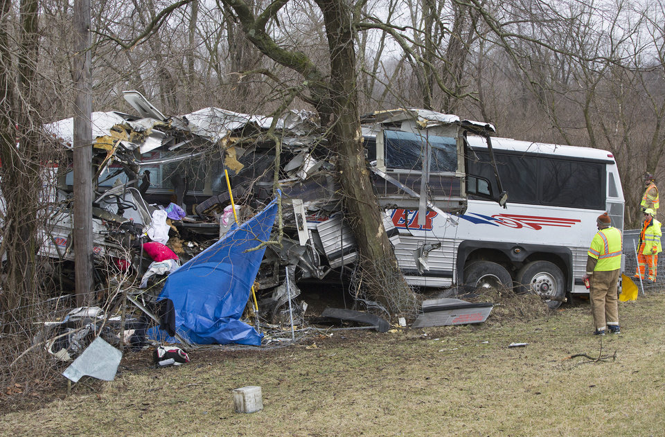 Photo - Authorities investigate a passenger bus crash on the Pennsylvania Turnpike on Saturday, March 16, 2013 near Carlisle, Pa.   Lacrosse players from Seton Hill University and three coaches were among the 23 people aboard when the bus crashed at about 9 a.m., turnpike spokeswoman Renee Colborn said. It's not clear what caused the crash, but state police were investigating, said Megan Silverstram of the Cumberland County public safety department. (AP Photo/The Patriot-News, Joe Hermitt)