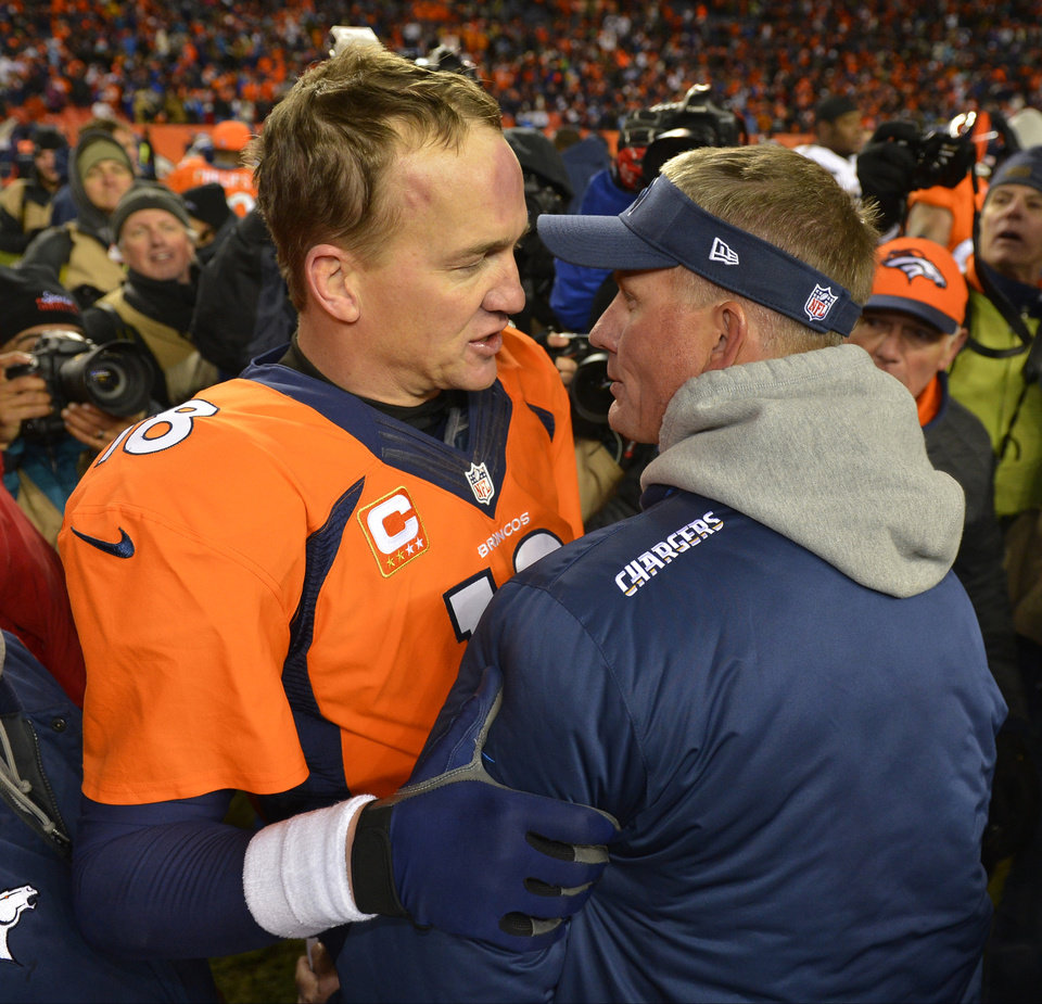 Photo - Denver Broncos quarterback Peyton Manning, left, greets San Diego Chargers coach Mike McCoy after the Broncos beat the Chargers 24-17 in an NFL AFC division playoff football game, Sunday, Jan. 12, 2014, in Denver. (AP Photo/Jack Dempsey)