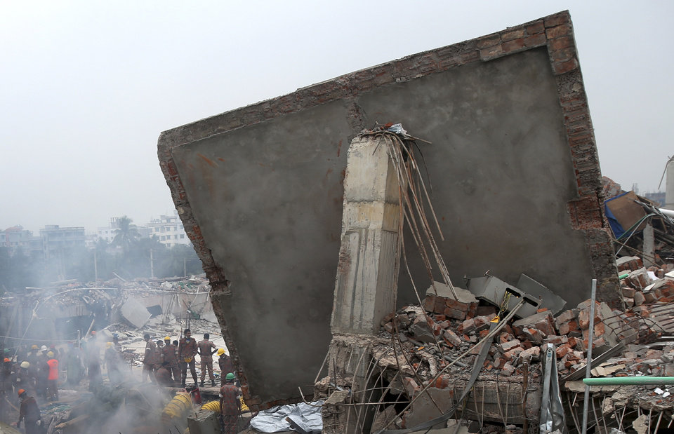 Photo - Rescue and recovery personnel prepare to dislodge the ceiling of the garment factory building which collapsed on Wednesday, in Savar, near Dhaka, Bangladesh, Monday April 29, 2013. Rescue workers in Bangladesh gave up hopes of finding any more survivors in the remains of a building that collapsed five days ago, and began using heavy machinery on Monday to dislodge the rubble and look for bodies - mostly of workers in garment factories there. At least 381 people were killed when the illegally constructed, 8-story Rana Plaza collapsed in a heap on Wednesday morning along with thousands of workers in the five garment factories in the building.(AP Photo/Wong Maye-E)