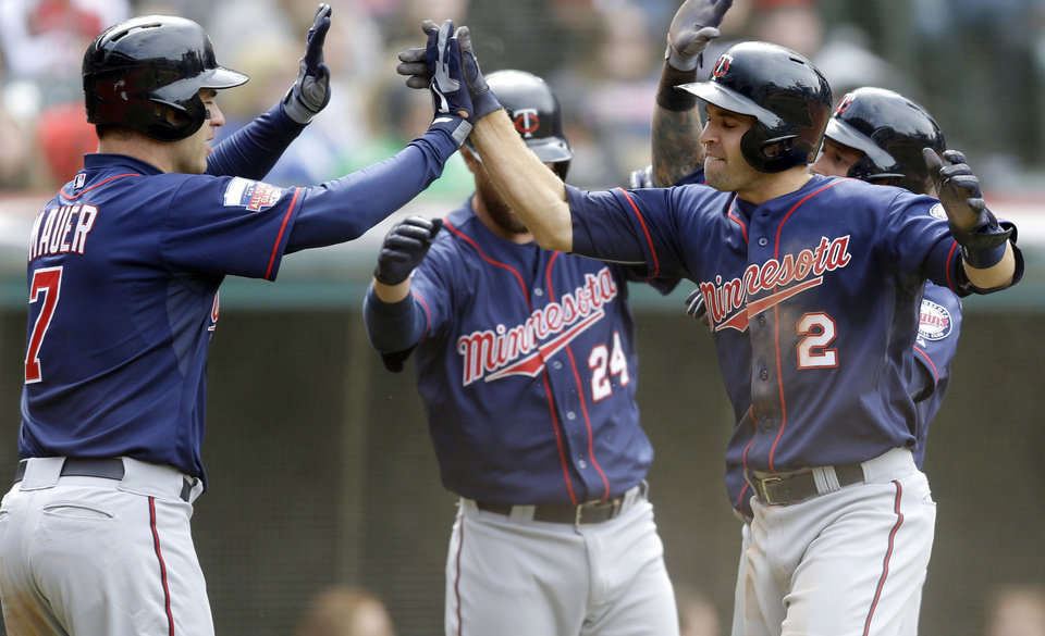 Photo - Minnesota Twins' Joe Mauer (7) and Brian Dozier (2) celebrate after scoring on a three-run double from Chris Colabello off Cleveland Indians relief pitcher Blake Wood during the sixth inning of a baseball game on Sunday, April 6, 2014, in Cleveland. Twins' Jason Bartlett also scored. (AP Photo/Tony Dejak)