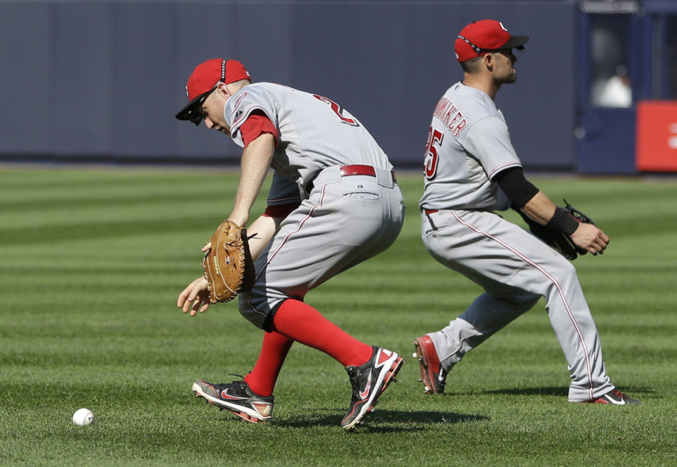 Photo - CORRECTS TO FIRST BASEMAN, TODD FRAZIER, LEFT, AND SECOND BASEMAN SKIP SCHUMAKER -Cincinnati Reds first baseman, Todd Frazier, left, and second baseman Skip Schumaker chase after a ball hit by New York Yankees' Brian McCann during the ninth inning of the game at Yankee Stadium Sunday, July 20, 2014 in New York. The hit scored the winning run and the Yankees defeated the Reds 3-2. (AP Photo/Seth Wenig)