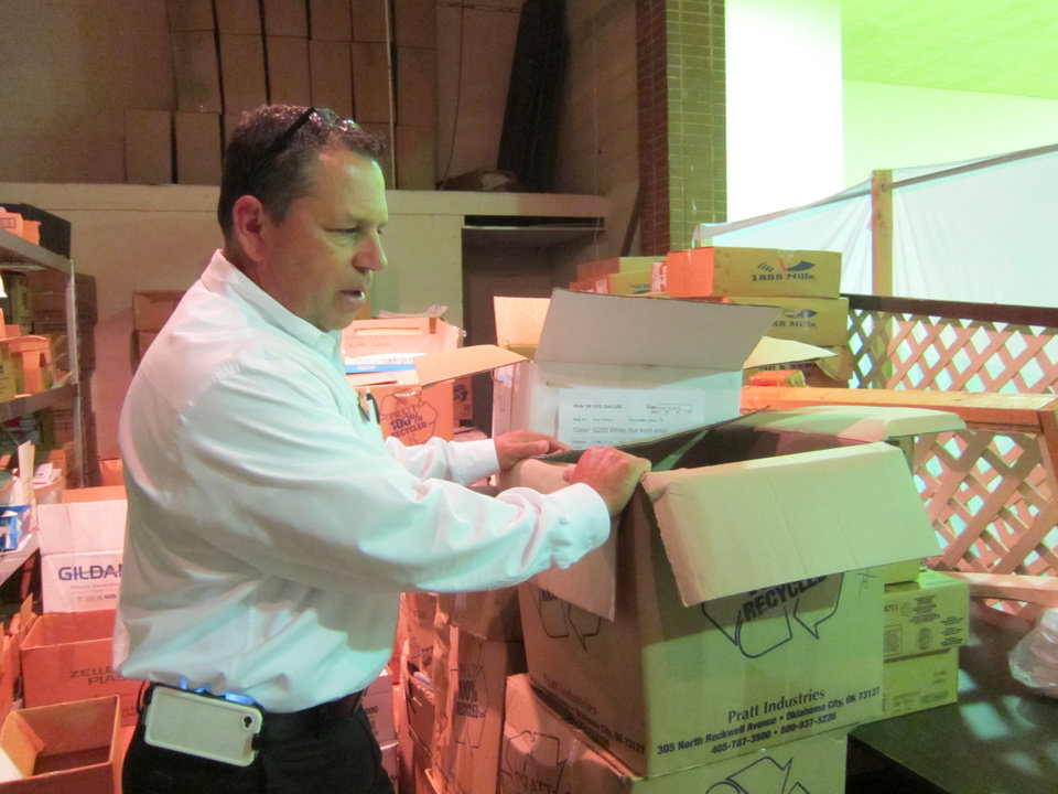 Photo -  Jeff Lara, director of operations for the Salvation Army Central Oklahoma Area Command, looks inside moving boxes in a warehouse at the organization's headquarters at 311 SW 5. Photo by Carla Hinton, The Oklahoman