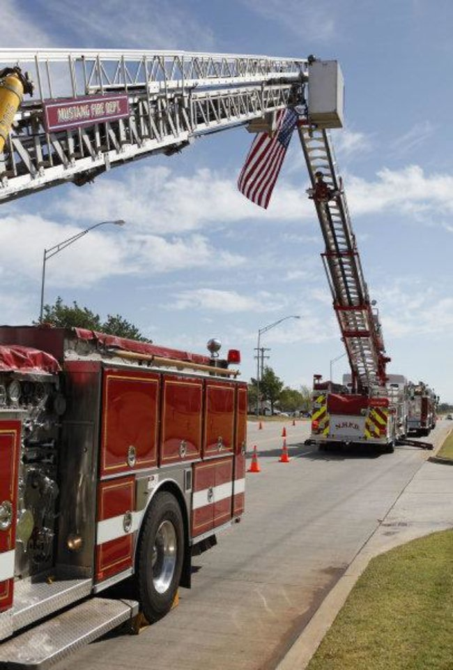 Photo - Ladder trucks from Mustang and Nichols Hills join to display the American flag outside The Bridge Assembly of God in Mustang on Saturday during the funeral of Nichols Hills Fire Chief Keith Bryan, who died Wednesday.  PAUL HELLSTERN