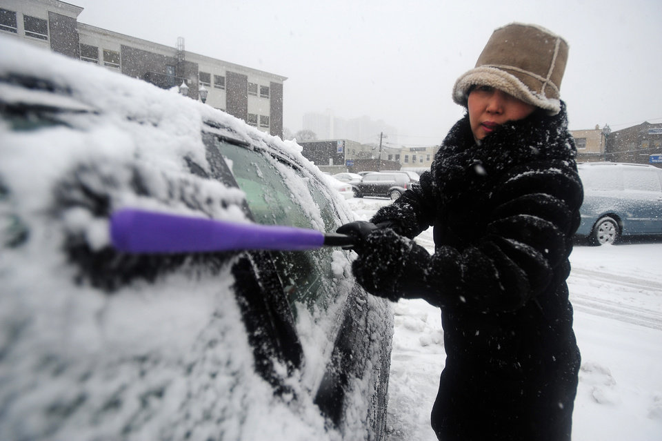 Photo - Edgewater resident Soonmee Lee cleans show from her car at the Municipal Parking Lot in Fort Lee, N.J. as a winter storm hits the region on Friday, Feb. 8, 2013. (AP Photo/The Record of Bergen County, Marko Georgiev) ONLINE OUT; MAGS OUT; TV OUT; INTERNET OUT;  NO ARCHIVING; MANDATORY CREDIT