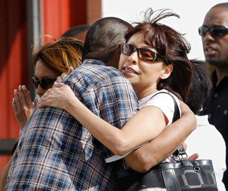 Photo - Mourners embrace Thursday following the funeral service for Rosalin Reynolds, 8, at the Watonga High School gym. Rosalin was found fatally stabbed in Watonga last week.  JIM BECKEL - The Oklahoman