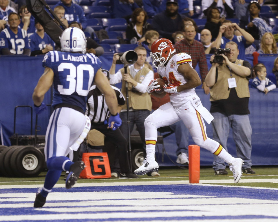 Photo - Kansas City Chiefs' Knile Davis (34) makes a 10-yard touchdown reception as Indianapolis Colts strong safety LaRon Landry (30) moves in during the second half of an NFL wild-card playoff football game Saturday, Jan. 4, 2014, in Indianapolis. (AP Photo/Michael Conroy)