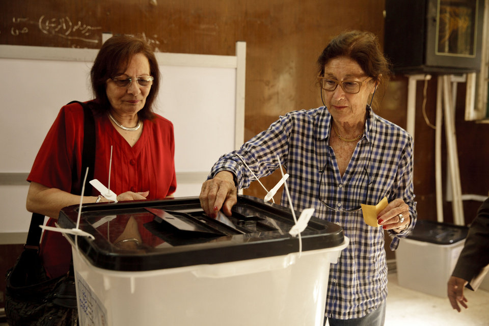 Photo - Egyptian women cast their ballots for President in an election that comes nearly a year after the military's ouster of the nation's first freely elected president, the Islamist Mohammed Morsi, in Cairo, Egypt, Monday, May 26, 2014. The man who removed Morsi, retired military chief Field Marshal Abdel-Fattah el-Sissi, is practically assured of a victory in the vote. (AP Photo/Maya Alleruzzo)