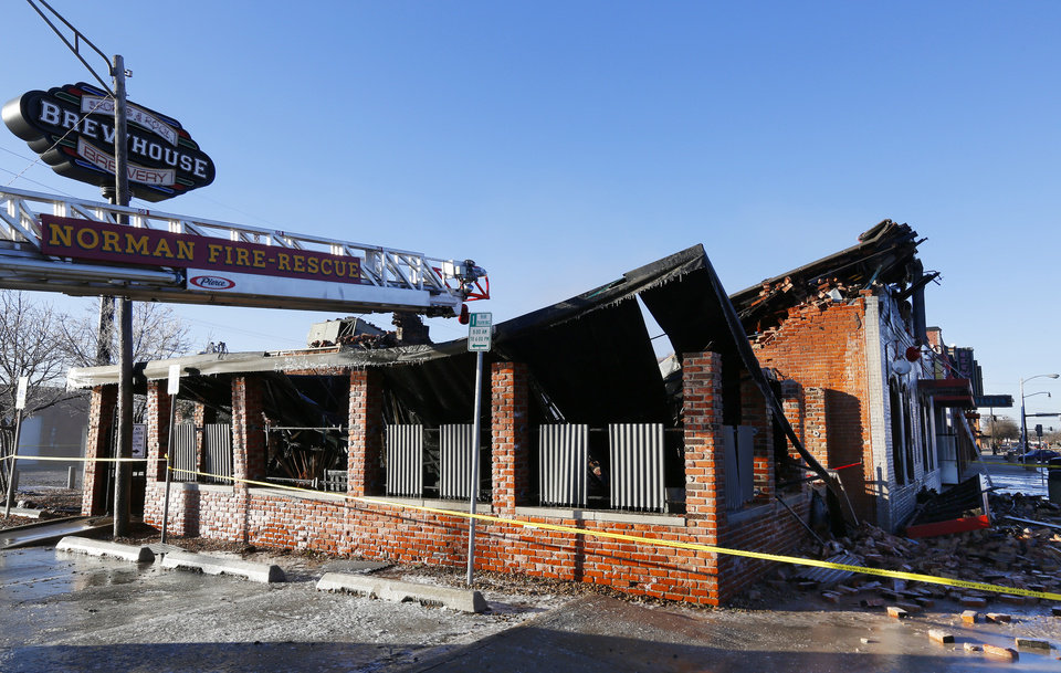 Photo -  An historic building in downtown Norman, most recently occupied by S&B Burger Joint, smolders Monday after an early morning fire swept through it. PHOTO BY PAUL B. SOUTHERLAND, THE OKLAHOMAN    PAUL B. SOUTHERLAND -