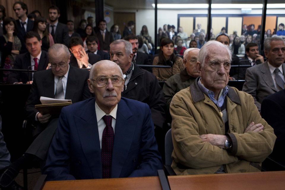 Photo -   Former Argentina's dictators Jorge Rafael Videla, left, and Reynaldo Bignone wait to listen the verdict of Argentina's historic stolen babies trial in Buenos Aires, Argentina, Thursday, July 5, 2012. The two former dictators and a handful of other retired military and police officials are accused of systematically stealing babies from leftists who were kidnapped and killed when a military junta ran the country three decades ago. (AP Photo/Natacha Pisarenko)