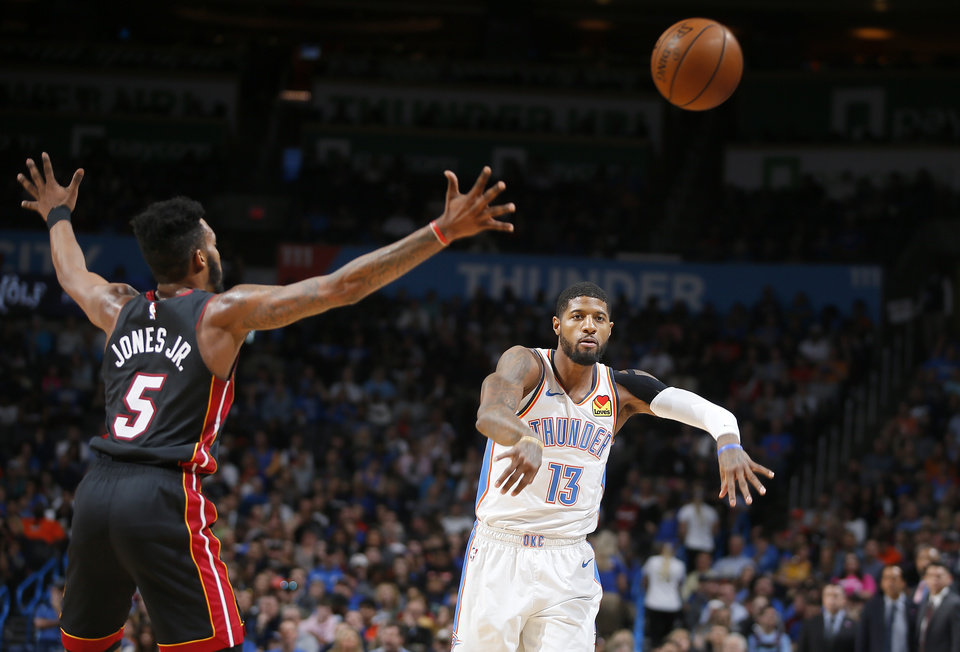 Photo - Oklahoma City's Paul George (13) passes the ball as Miami's Derrick Jones Jr. (5) defends during an NBA basketball game between the Oklahoma City Thunder and the Miami Heat at Chesapeake Energy Arena in Oklahoma City, Monday, March 18, 2019. Photo by Bryan Terry, The Oklahoman