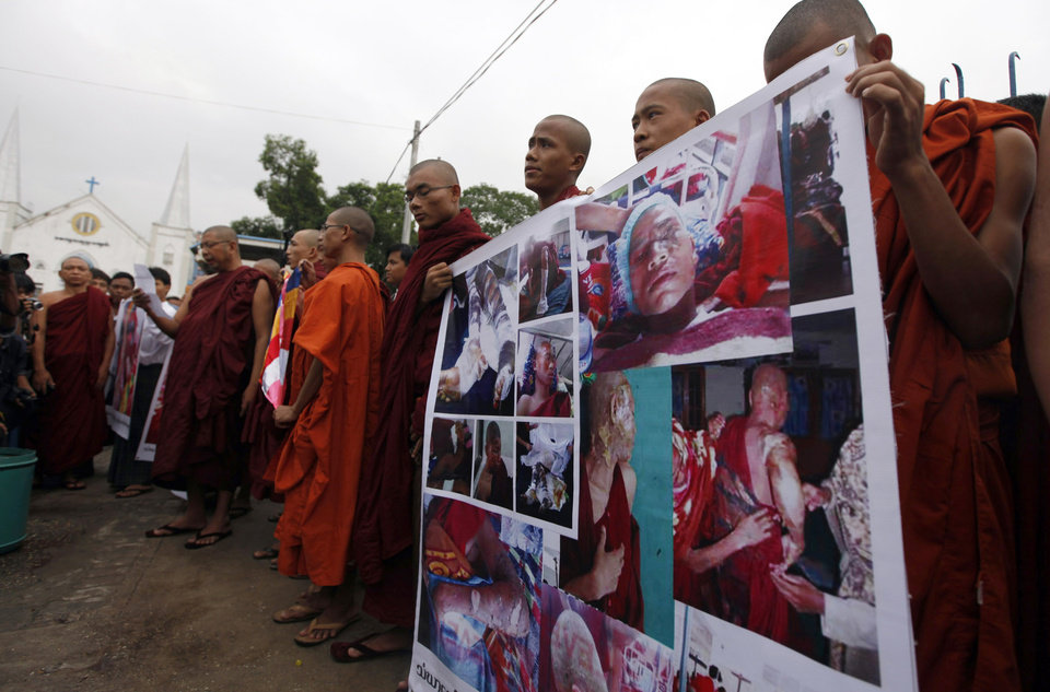 Photo - Buddhist monks hold prayers with photos of monks injured in crackdown at the Letpadaung copper mine in Monywa, northwestern Myanmar, in Yangon, Myanmar, Friday, Nov. 30, 2012. Opposition leader Aung San Suu Kyi publicly criticized the forcible crackdown on protesters at the mine and said Friday that the public needed an explanation of the violence that injured dozens, including Buddhist monks. (AP Photo/Khin Maung Win)