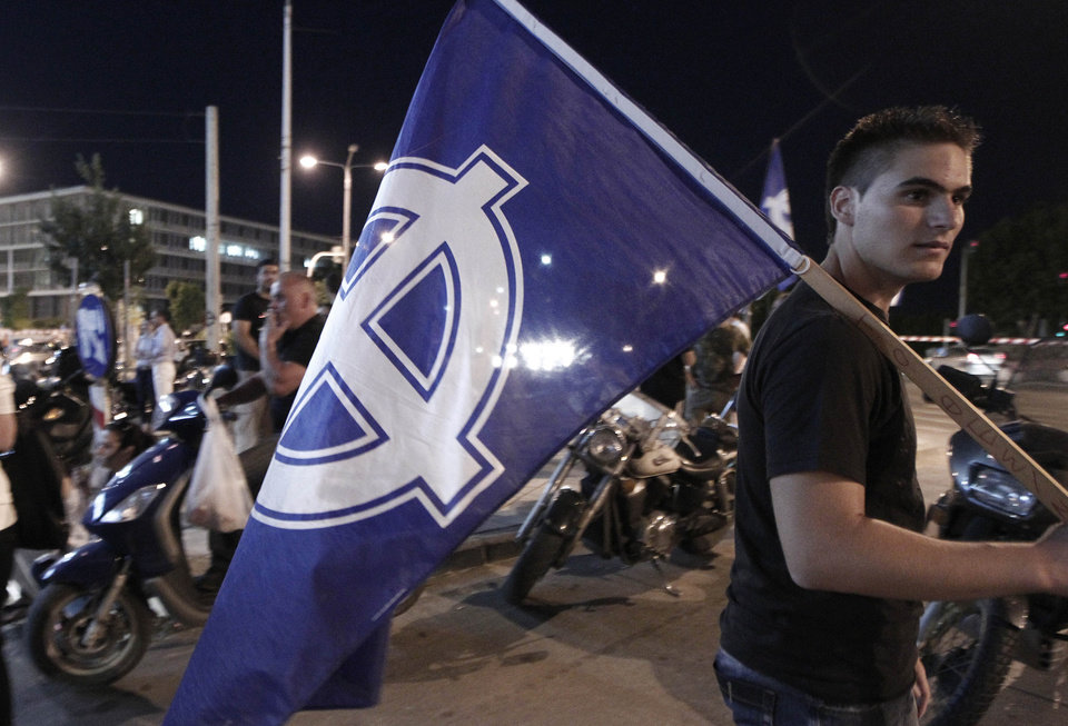 Photo -   Supporters of the far right party of Golden Dawn celebrate the results of the elections outside their headquarters office in Thessaloniki, Greece Sunday, June 17, 2012. Official projections showed the Golden Dawn party returning to the 300-member parliament with 18 seats, just three fewer than it had won in an inconclusive election on May 6, when no party won enough votes to form a government amid a deep financial crisis that threatens Greece's place in the Eurozone and could hurt the global economy. The pro-bailout New Democracy party came in first Sunday in Greece's national election, and its leader has proposed forming a pro-euro coalition government. (AP Photo/Dimitri Messinis)