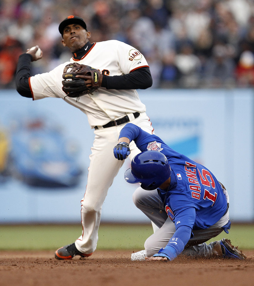 Photo - San Francisco Giants third baseman Joaquin Arias, top, gets the force out on Chicago Cubs' Darwin Barney during the fifth inning of a baseball game on Saturday, July 27, 2013, in San Francisco. (AP Photo/Tony Avelar)