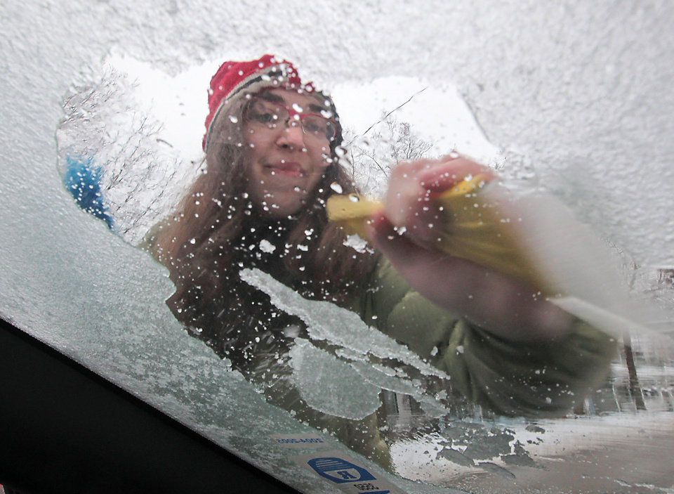 Photo - Julia Rhodes works to remove an accumulation of ice from the windshield of her car in Madison, Wis. after freezing rains moved through the area Friday, Dec. 20, 2013. (AP Photo/John Hart, Wisconsin State Journal)