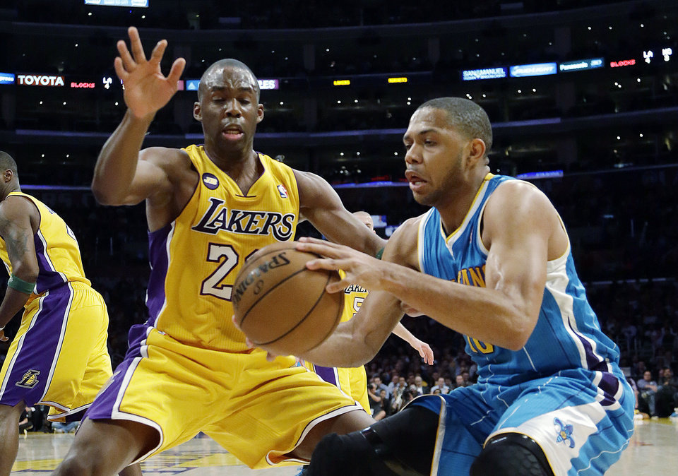 Photo - New Orleans Hornets guard Eric Gordon (10) and Los Angeles Lakers guard Jodie Meeks (20) battle in the first half of an NBA basketball game in Los Angeles Tuesday, April 9, 2013.  (AP Photo/Reed Saxon)