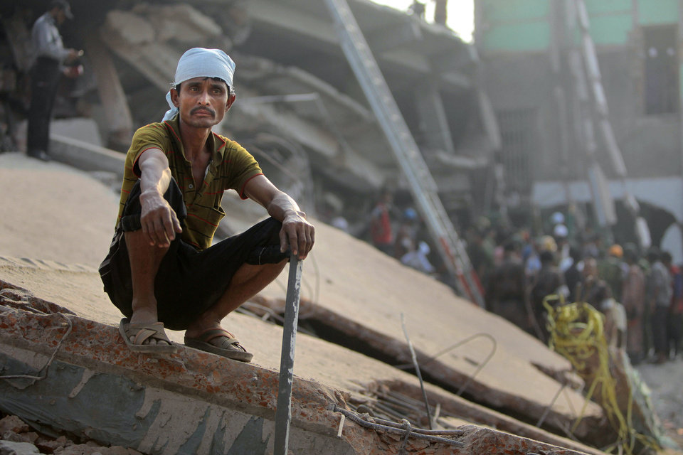 Photo - A Bangladeshi rescue worker takes a break at the site of a building that collapsed Wednesday in Savar, near Dhaka, Bangladesh,Thursday, April 25, 2013. By Thursday, the death toll reached at least 194 people as rescuers continued to search for injured and missing, after a huge section of an eight-story building that housed several garment factories splintered into a pile of concrete.  (AP Photo/A.M.Ahad)