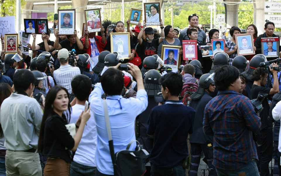 Photo - Red shirt supporters stand in front of a line of riot police while holding pictures of people who died during a crackdown on demonstrators in May 2010, as former Thai Prime Minister Abhisit Vejjajiva and former Deputy Prime Minister Suthep Thuagsuban arrive at the Department of Special Investigation to acknowledge the murder charges filed against them, Thursday, Dec. 13, 2012, in Bangkok, Thailand. The Thai DSI  filed murder charges against Suthep and Abhisit for their roles in the deadly 2010 crackdown on anti-government protesters that left more than 90 people dead and about 1,800 injured.  (AP Photo/Apichart Weerawong)