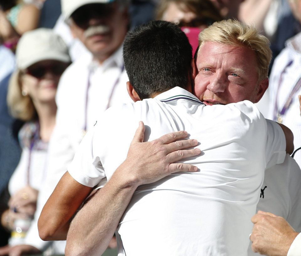 Photo - Novak Djokovic of Serbia celebrates with his coach Boris Becker, right, in the players box after defeating Roger Federer of Switzerland in the men's singles final at the All England Lawn Tennis Championships in Wimbledon, London, Sunday July 6, 2014. (AP Photo/Pavel Golovkin)