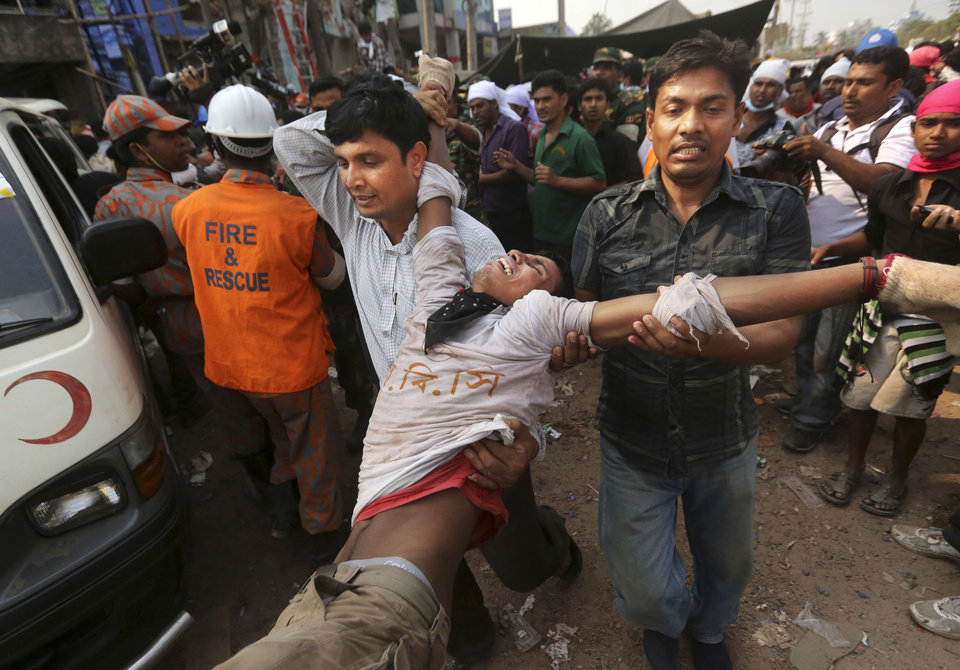 Photo - A Bangladeshi rescue worker who was injured during a stampede caused by crowd panic over the rumor a section of the building might collapse, is carried at the site of a building that collapsed Wednesday in Savar, near Dhaka, Bangladesh, Friday, April 26, 2013.   Crews bored deeper Friday into the wreckage of a garment-factory building that collapsed two days earlier, hoping for miracle rescues that would prevent the death toll from rising much higher, as angry relatives of the missing clashed with police. (AP Photo/Kevin Frayer)