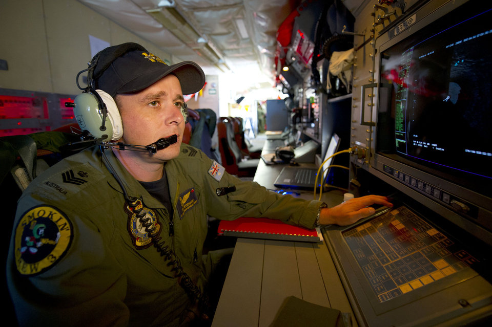 Photo - In this Wednesday, March 19, 2014 photo released by the Australia Defence Department, Royal Australian Air Force Airborne Electronics Analyst, Flight Sgt. Tom Stewart from 10 Squadron, on board an AP-3C Orion watches a radar screen over the Southern Indian Ocean off the Western Australian coast during a search operation for the missing Malaysia Airlines flight MH370. Australian Prime Minister Tony Abbott said Thursday that two objects possibly related to the missing flight have been spotted on satellite imagery in the Indian Ocean and an air force aircraft was diverted to the area to try to locate them. (AP Photo/Australia Defence Department, Hamish Paterson)