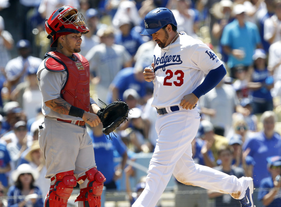 Photo - Los Angeles Dodgers' Adrian Gonzalez (23) scores in front of St. Louis Cardinals catcher Yadier Molina, left, on a sacrifice fly to center field by Dodgers' Juan Uribe in the fourth inning of a baseball game on Sunday, June 29, 2014, in Los Angeles. (AP Photo/Alex Gallardo)