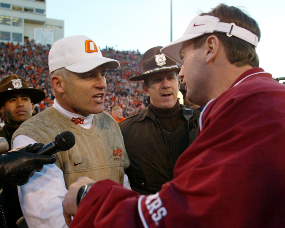 Photo - BEDLAM COLLEGE FOOTBALL, OU, OSU: Oklahoma State head coach Les Miles, left, greets Oklahoma head coach Bob Stoops, right, meet at midfield following Oklahoma States' 38-28 victory over Oklahoma in Stillwater, Okla., Saturday, Nov. 30, 2002. .  (AP Photo/Sue Ogrocki)