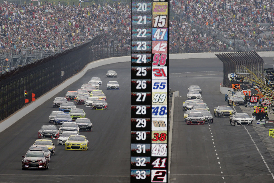 Photo - Cars on different pit strategies enter pit lane while others stay on the track in a caution period during the NASCAR Brickyard 400 auto race at Indianapolis Motor Speedway in Indianapolis, Sunday, July 27, 2014.  (AP Photo/AJ Mast)