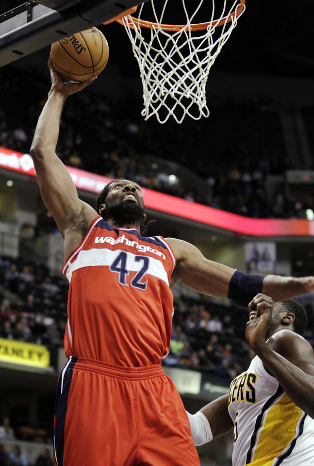 Washington Wizards center Nene (42), of Brazil, dunks around Indiana Pacers center Roy Hibbert during the first half of an NBA basketball game, Wednesday, Jan. 2, 2013, in Indianapolis. (AP Photo/AJ Mast)