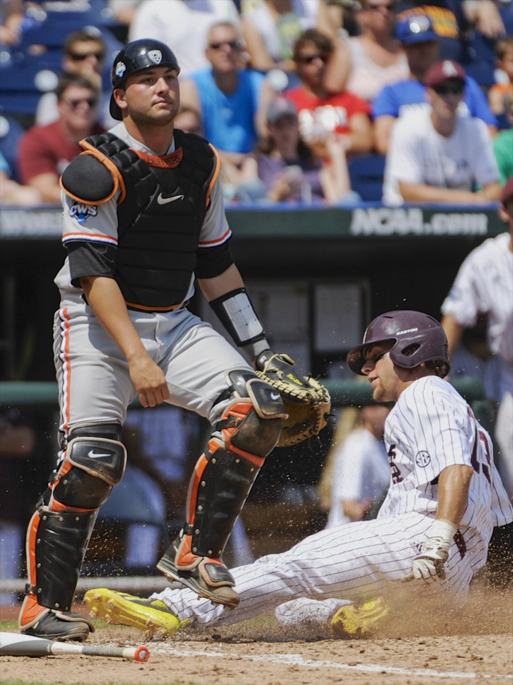 Photo - Mississippi State's Brett Pirtle, right, scores on an RBI single by C.T. Bradford as Oregon State catcher Jake Rodrigues looks away during the fourth inning of an NCAA College World Series baseball game in Omaha, Neb., Friday, June 21, 2013. (AP Photo/Francis Gardler)