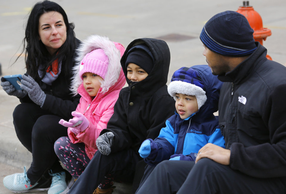 Photo - Jerald, right, and Hailey, left, Harrison sit on the curb with their children, Ava, 5, Jayden, 7, and Jayce, 4,  while trying to keep warm in sub-freezing temperatures as they watch the Martin Luther King, Jr. Day parade in Oklahoma City on Monday, Jan. 15, 2018. Photo by Jim Beckel, The Oklahoman