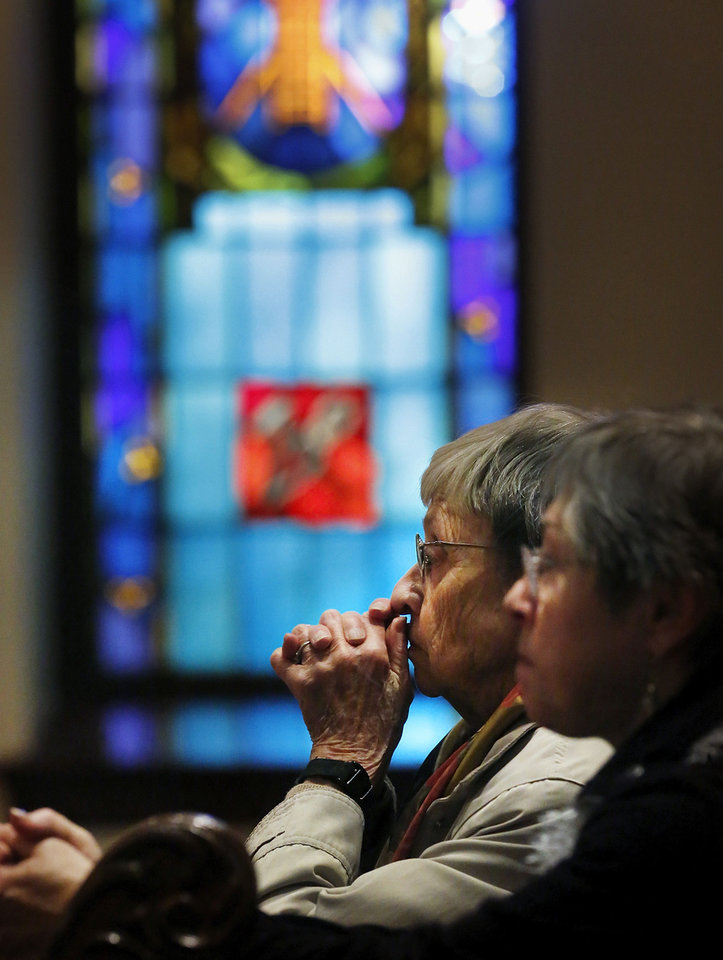 Photo - Two women pray Monday during a remembrance service in front of a stained-glass window at St. Paul's Episcopal Cathedral. The service, which honored those who died Friday in a shooting massacre in Newtown, Conn., attracted about 75 people, who gathered for prayer and song inside the church in downtown Oklahoma City.  Photo by Jim Beckel, The Oklahoman
