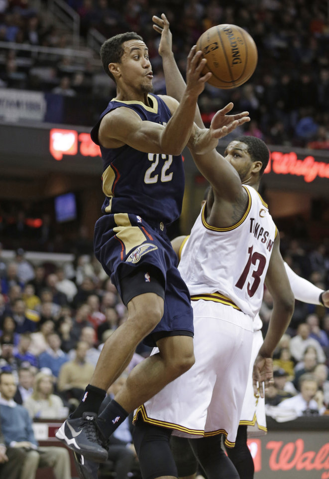Photo - New Orleans Pelicans' Brian Roberts (22) passes around Cleveland Cavaliers' Tristan Thompson (13), of Canada, during the first quarter of an NBA basketball game, Tuesday, Jan. 28, 2014, in Cleveland. (AP Photo/Tony Dejak)