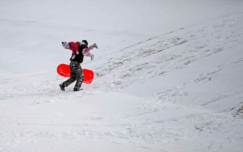 Gary Bergeron carries his daughter Rachel, 5, up a hill to sled after a winter storm left a blanket of snow in their northwest Oklahoma City area neighborhood near 164th and Pennsylvania, Friday, December 6, 2013. Photo by Bryan Terry, The Oklahoman