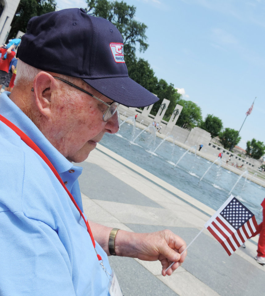 Photo - Alvin Martin, Leedy, waves a flag Wednesday during an Oklahoma Honor Flights trip to Washington, D.C.  Photo by Bryan Painter, The Oklahoman   Bryan Painter