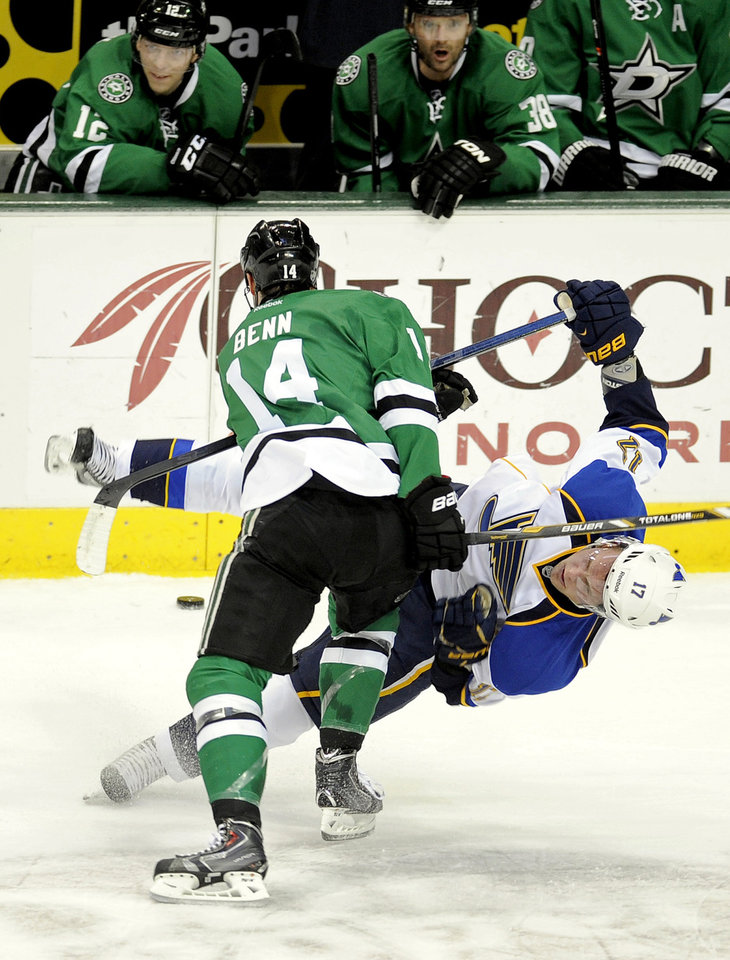 Dallas Stars left wing Jamie Benn (14) checks St. Louis Blues center Vladimir Sobotka (17) in front of the Stars bench during the first period of an NHL hockey game, Sunday, Dec. 29, 2013, in Dallas. (AP Photo/Matt Strasen)
