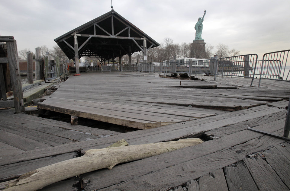 Photo - Boards of the passenger dock of Liberty Island are askew, damaged from Superstorm Sandy, in New York, Friday, Nov. 30, 2012. Tourists in New York will miss out for a while on one of the hallmarks of a visit to New York, seeing the Statue of Liberty up close. Though the statue itself survived Superstorm Sandy intact, damage to buildings and Liberty Island's power and heating systems means the island will remain closed for now, and authorities don't have an estimate on when it will reopen. (AP Photo/Richard Drew)