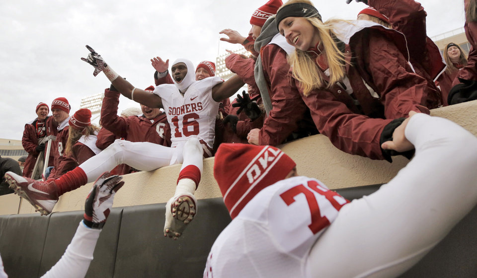 Photo - Oklahoma's Jaz Reynolds (16) celebrates with fans after the Bedlam college football game between the Oklahoma State University Cowboys (OSU) and the University of Oklahoma Sooners (OU) at Boone Pickens Stadium in Stillwater, Okla., Saturday, Dec. 7, 2013. Photo by Chris Landsberger, The Oklahoman