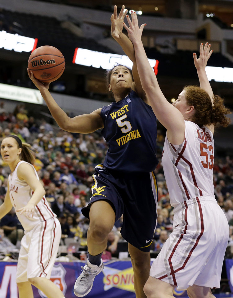 Photo - West Virginia' Averee Fields (5) goes up for a shot as Oklahoma's Joanna McFarland (53) defends in the first half of an NCAA college basketball game in the Big 12 women's tournament Saturday, March 9, 2013, in Dallas. (AP Photo/Tony Gutierrez)