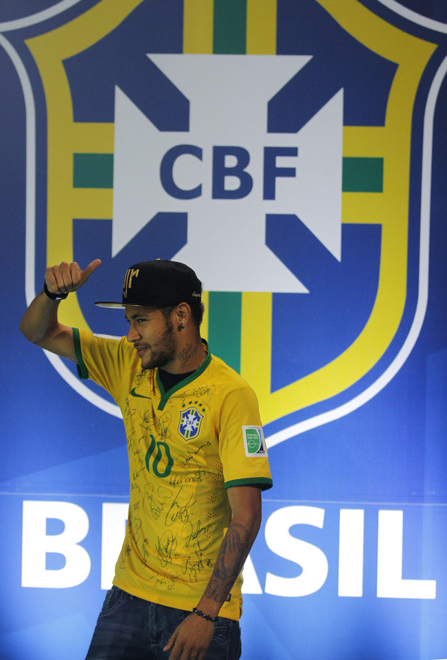 Photo - Brazil's Neymar gives the thumbs up, as he leaves after a press conference at the Granja Comary training center in Teresopolis, Brazil, Thursday, July 10, 2014. The Brazilian soccer star is back on his feet after suffering a broken vertebrae during a World Cup soccer match against Colombia. Brazil will be disputing a third place finish, without its star on Saturday. (AP Photo/Leo Correa)