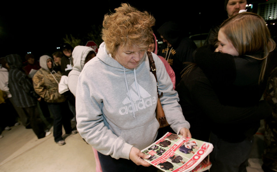 Photo - Mary Ray of Norman looks over her Kohl's ad while waiting in line at the Norman store for after Thanksgiving sales Fri. Nov. 27, 2009. Photo by Jaconna Aguirre, The Oklahoman.