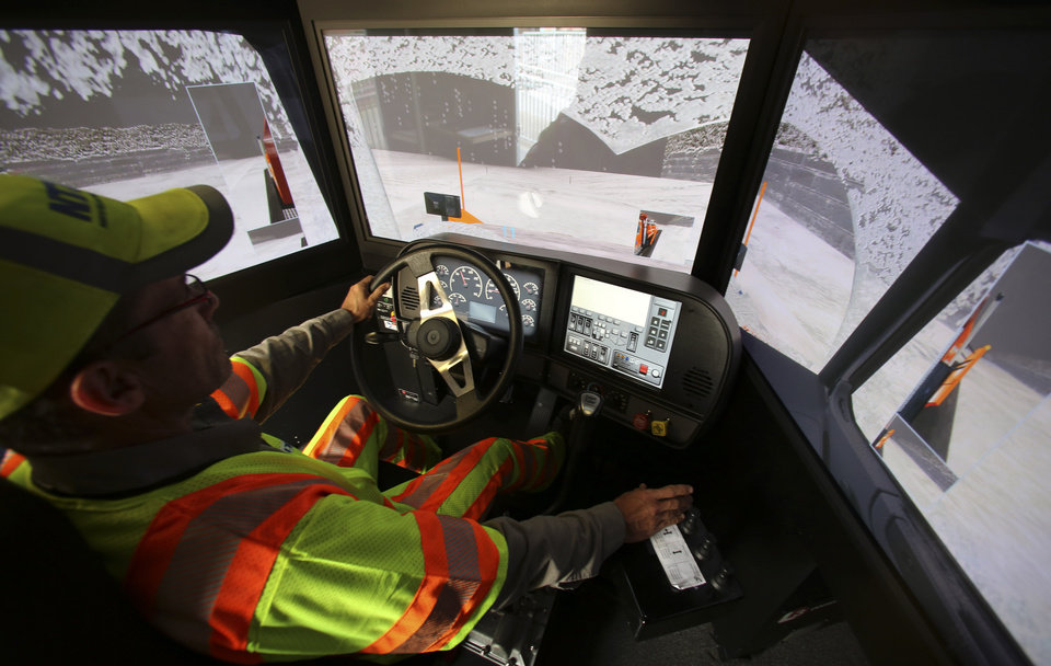 Driver Terence Mundt operates a snowplow simulator during a North Texas Tollway Authority training class in Plano, Texas, Thursday, Nov. 15, 2012.  The NTTA is using the computer generated simulator to help snowplow operators become better at handling slick roads in a region not used to ice and snow. Highway officials in at least nine states are using the sophisticated simulator to give plow drivers a chance to practice snow removal in any weather. It works like a video game, recreating slick pavement, poor visibility and even children or animals bolting across the road. (AP Photo/LM Otero)