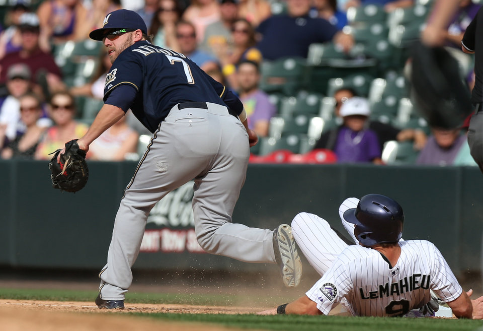 Photo - Milwaukee Brewers first baseman Mark Reynolds, left, fields the throw to put out Colorado Rockies' DJ LeMahieu, right, at first base on the back end of a double play hit into by pinch-hitter Charlie Culberson in the ninth inning of the Brewers' 9-4 victory in a baseball game in Denver, Saturday, June 21, 2014. LeMahieu was put out after straying too far from the bag as Brewers' rightfielder Ryan Braun caught a line drive off the bat of Culberson. (AP Photo/David Zalubowski)