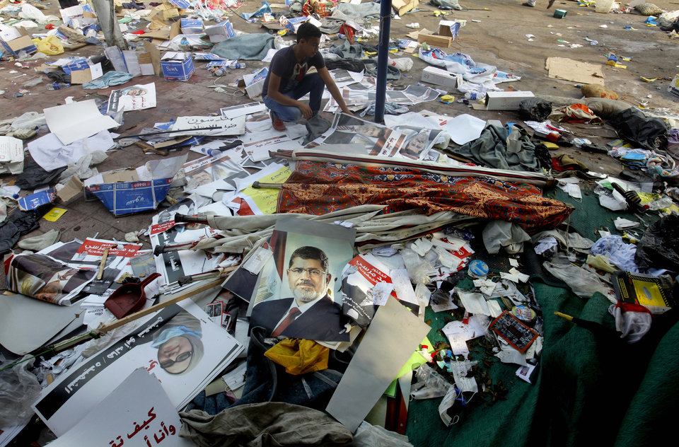 Photo - An Egyptian searches for valuables among debris in a protest camp in Nahda Square, Giza, Cairo, Egypt, Thursday, Aug. 15, 2013. Egypt faced a new phase of uncertainty on Thursday after the bloodiest day since its Arab Spring began, with over 300 people reported killed and thousands injured as police smashed two protest camps of supporters of the deposed Islamist president. Wednesday's raids touched off day-long street violence that prompted the military-backed interim leaders to impose a state of emergency and curfew, and drew widespread condemnation from the Muslim world and the West, including the United States. (AP Photo/Amr Nabil)